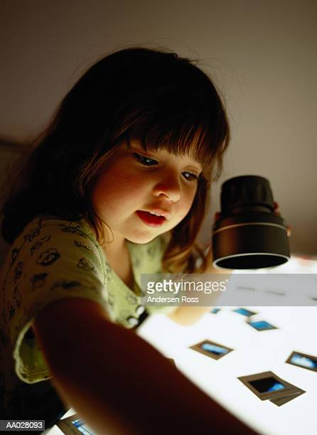 Girl (3-5) looking at slide on light table, high section