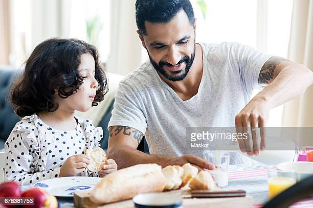 Girl looking at smiling father pouring milk in glass during breakfast at home