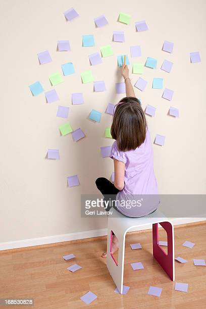 Girl looking at sticky notes on wall