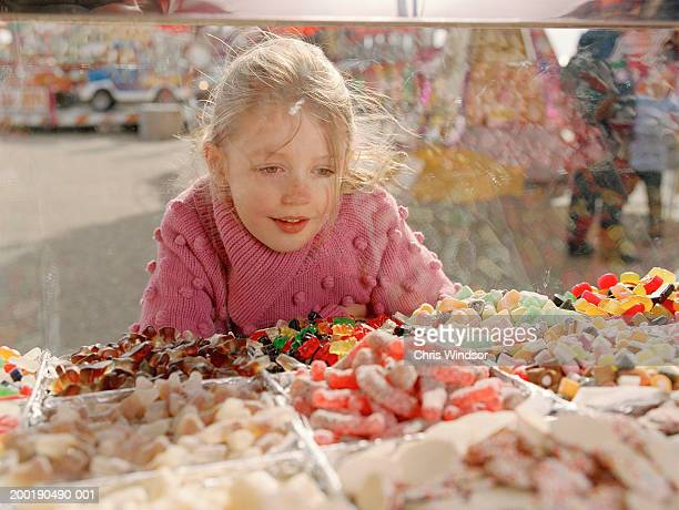 Girl (7-9) looking at sweets in glass counter