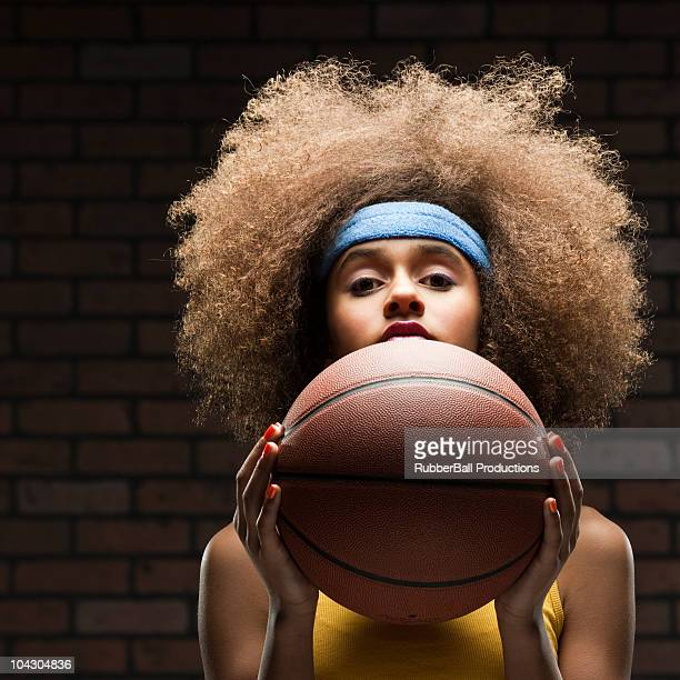 La jeune fille à la recherche dans la caméra tenant une basket