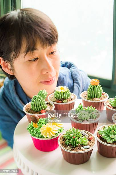 Girl looking at the Cup cakes decorated like little cactus