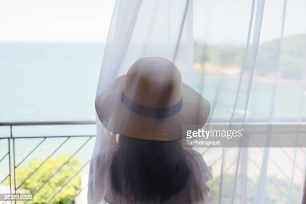 Girl looking at the sea in a curtain