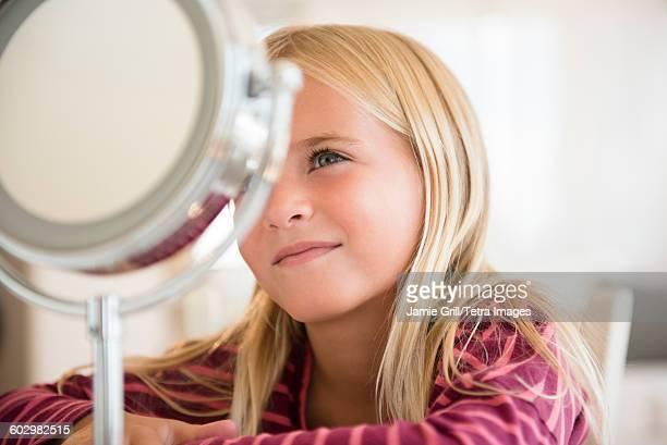 girl (6-7) looking at vanity mirror - ijdel stockfoto's en -beelden