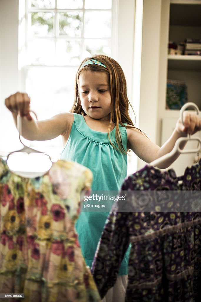 girl (6yrs) looking at which dress to wear : Stock Photo