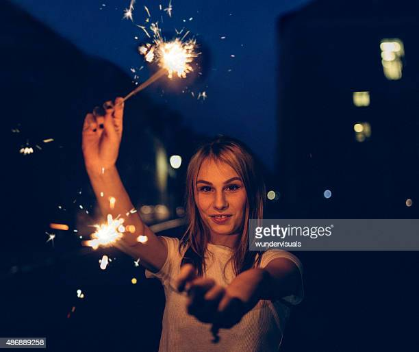 Girl looking at you with sparklers at night in city
