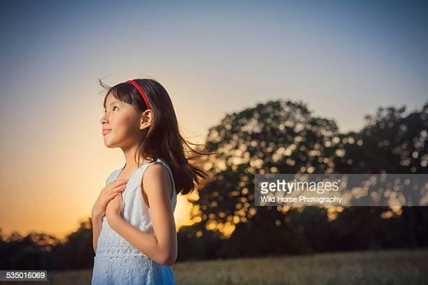 girl looking away in sunset - girl blowing horse - fotografias e filmes do acervo