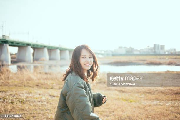 girl looking back with smile - yusuke nishizawa stock pictures, royalty-free photos & images