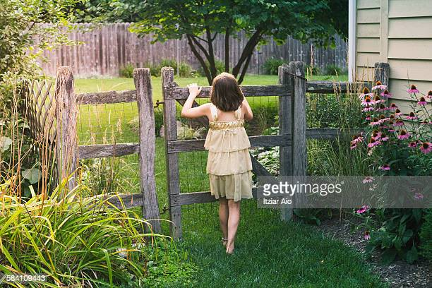 Girl looking curiously through a fence