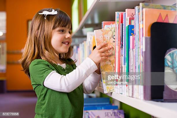 Girl looking for library book