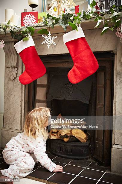 girl looking for santa in fireplace - stockings no shoes stock pictures, royalty-free photos & images