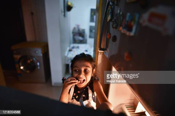 girl looking for some snacks in the refrigerator - india summer stock pictures, royalty-free photos & images
