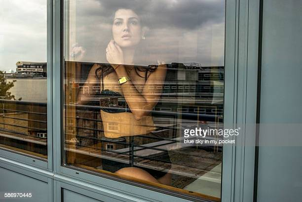 a girl looking from a bedroom window - erin james stock-fotos und bilder