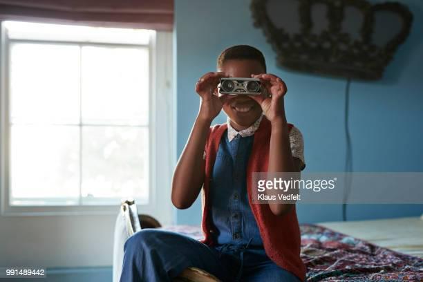 Girl looking in camera with retro binoculars