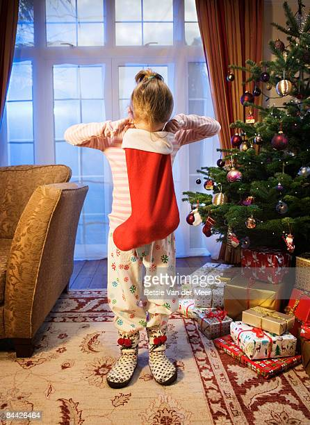 Girl looking in christmas stocking.