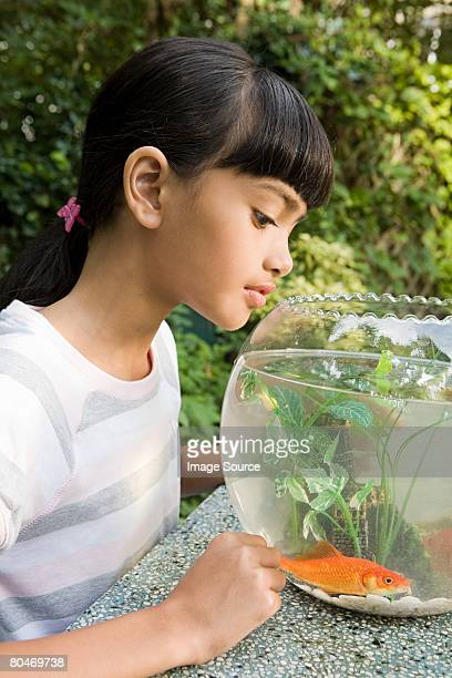 Girl looking in goldfish bowl