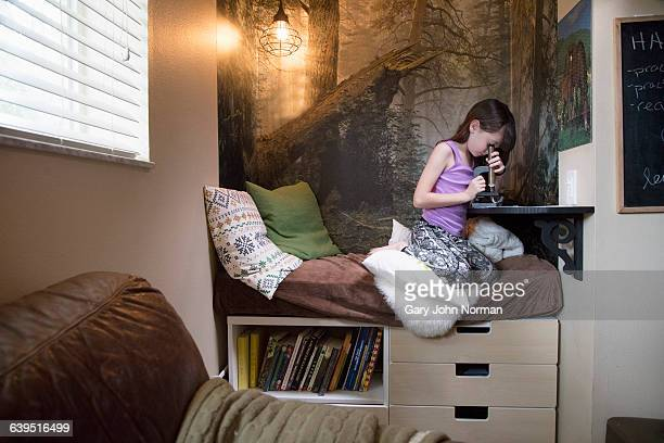 Girl looking in microscope at home