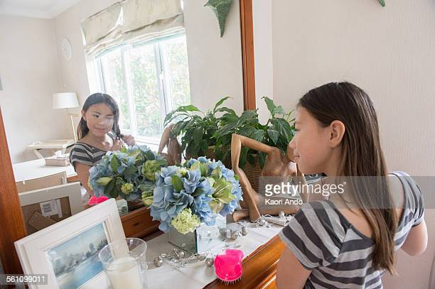 Girl looking in mirror and fiddling with her hair