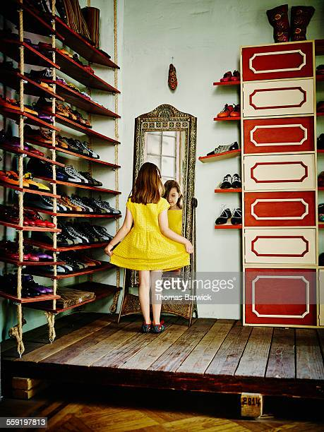 Girl looking in mirror while trying on shoes