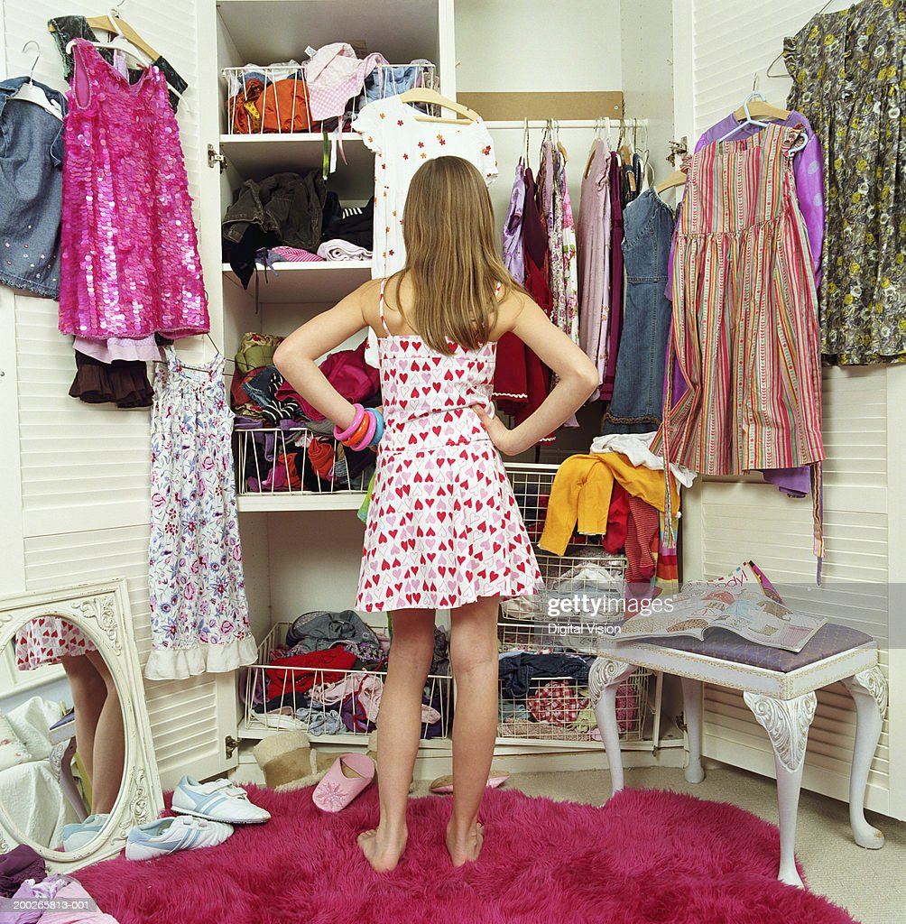 Girl (9-11) looking in wardrobe, hands on hips, rear view : Stock Photo