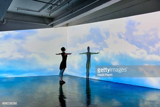 girl looking into a large scale projected image of skies - cloudscape stock pictures, royalty-free photos & images