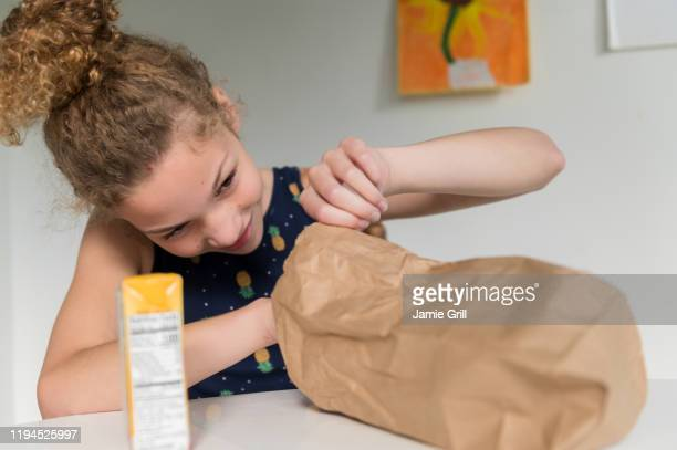 girl looking into brown paper bag - lunch bag stock pictures, royalty-free photos & images