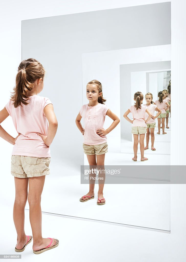 Girl (4-5) looking into her reflections in mirror : Stock Photo