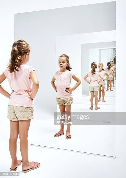 girl (4-5) looking into her reflections in mirror - girl in mirror stock-fotos und bilder
