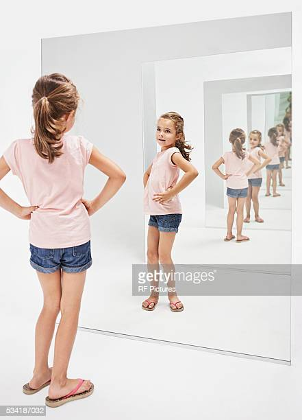 girl (4-5) looking into her reflections in mirror - bottomless girl stock pictures, royalty-free photos & images