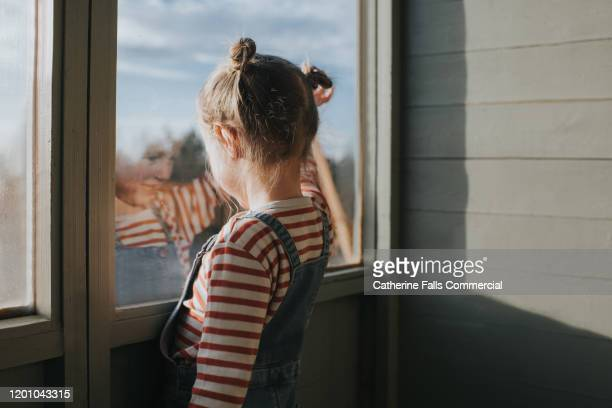 girl looking out a window - waving stock pictures, royalty-free photos & images