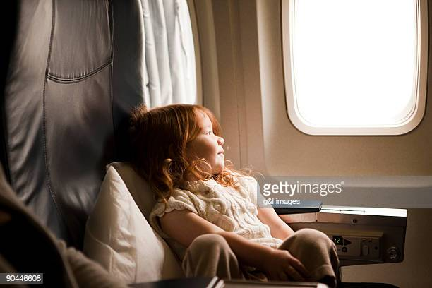 girl (2-3) looking out airplane window