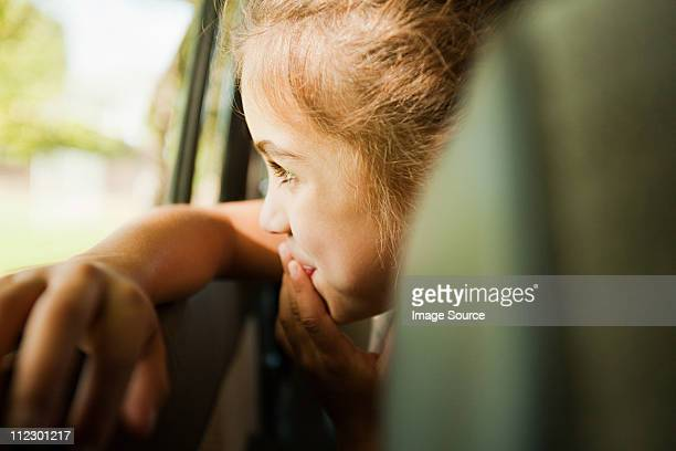 girl looking out car window - looking through window stock pictures, royalty-free photos & images