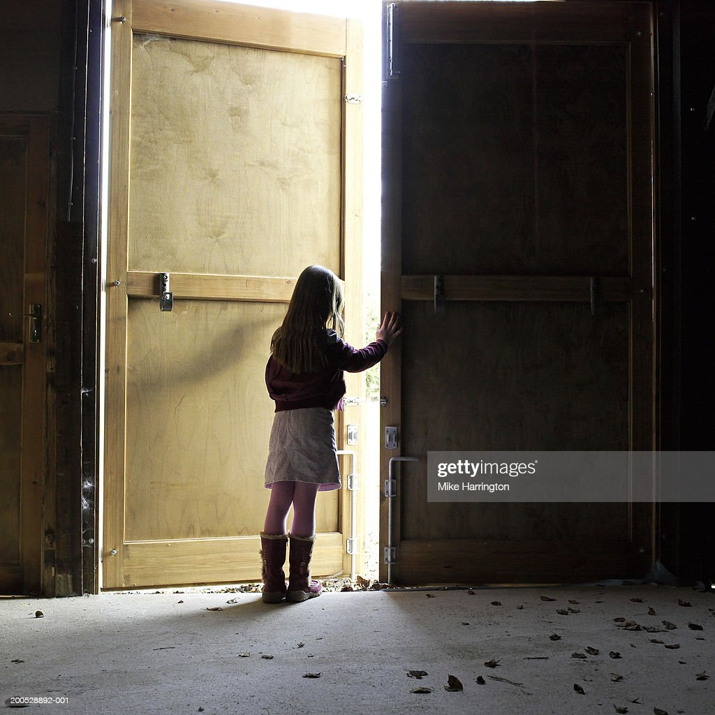 looking out door. Girl (7-9) Looking Out Door Of Barn, Rear View : Stock O
