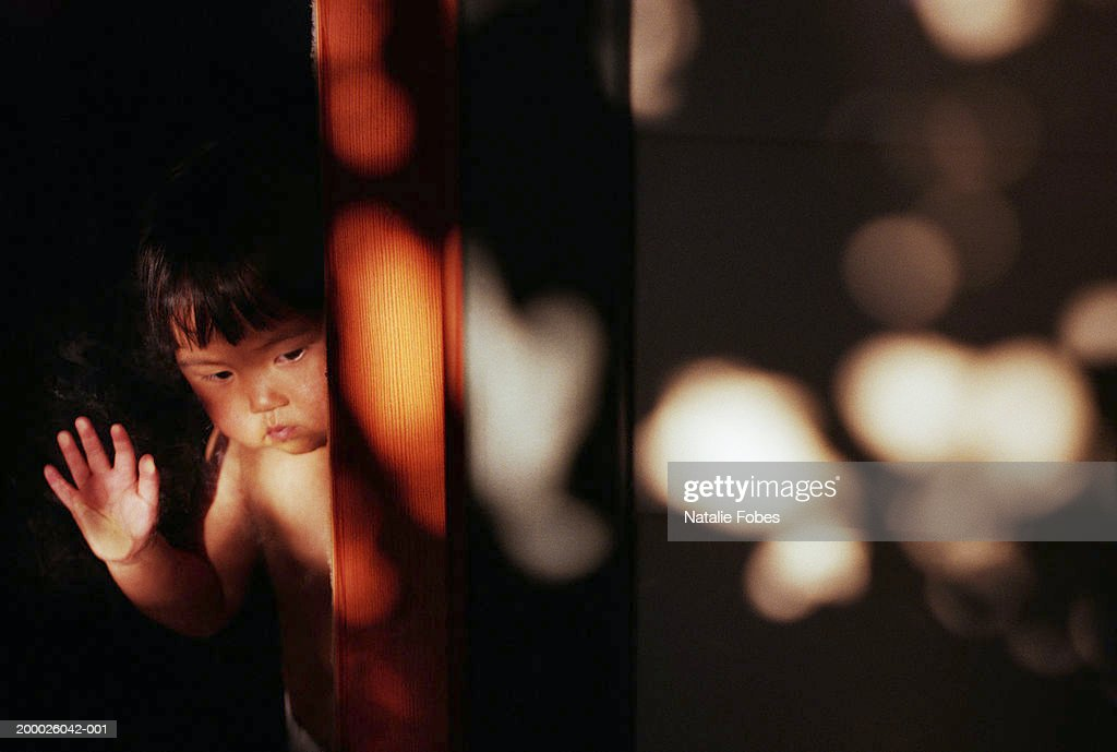 Girl Looking Out From Behind Glass Door Stock Photo Getty Images