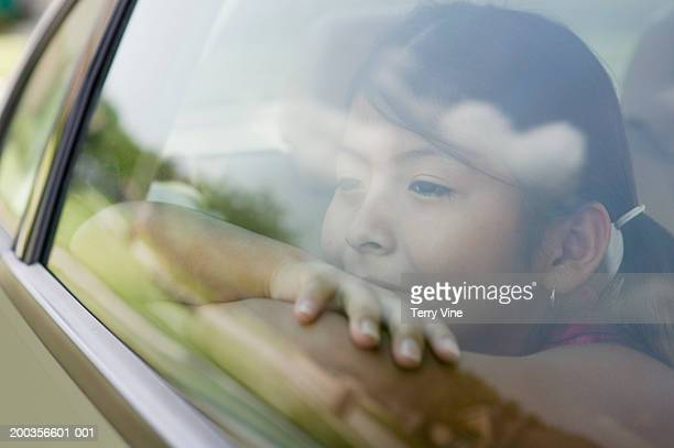 Girl (7-9) looking out of car window