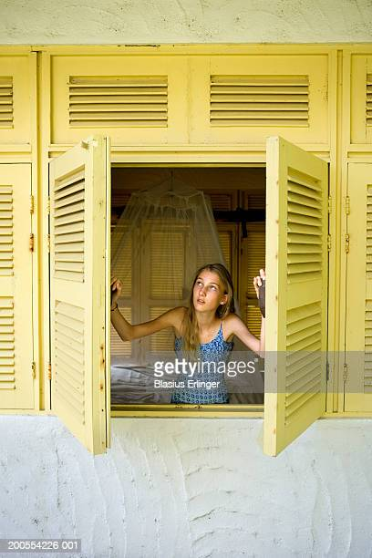 Girl (12-13) looking out of shutter window