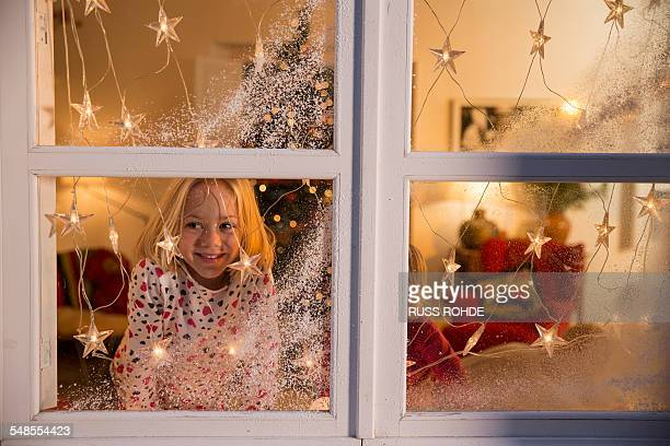Girl looking out of window with Christmas decorations