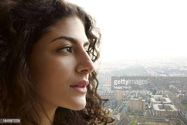 Girl looking out on the city from her flat