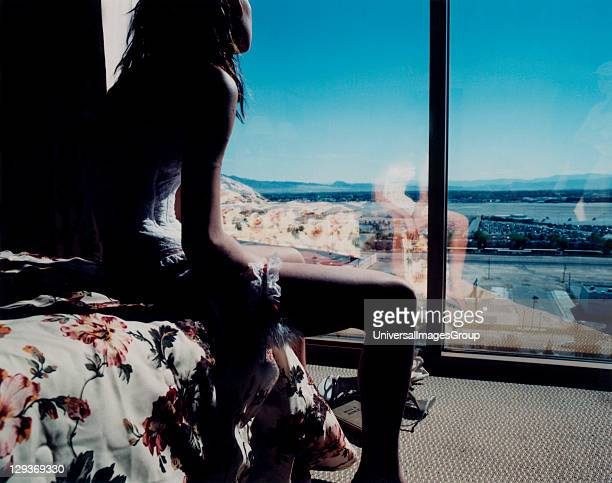 Girl looking out over a desert town through glass doors, USA 2004