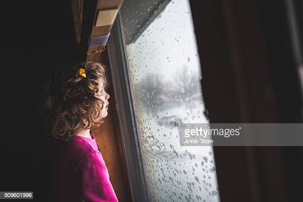 Girl looking out Snowy Window