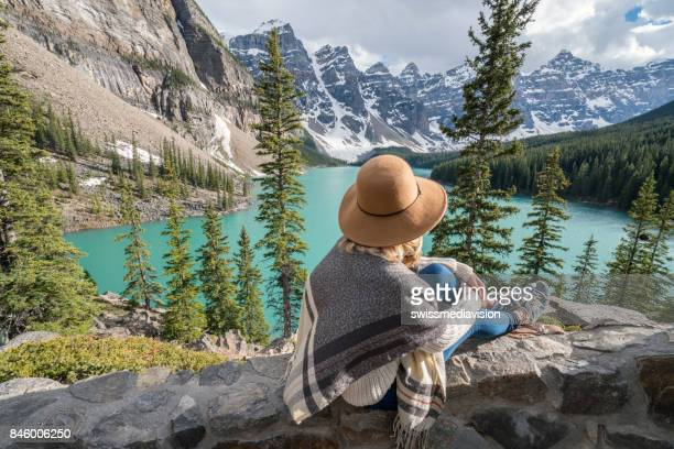 Girl looking out spectacular mountain lake landscape at Moraine lake