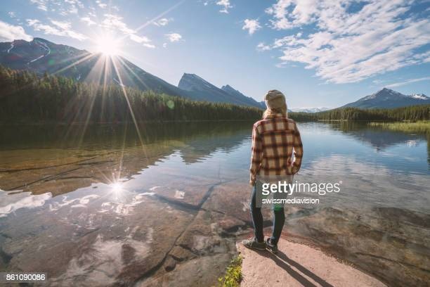 Girl looking out spectacular mountain lake landscape
