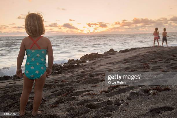 girl looking out to sea at sunrise, blowing rocks preserve, jupiter island, florida, usa - blowing rocks preserve stock photos and pictures