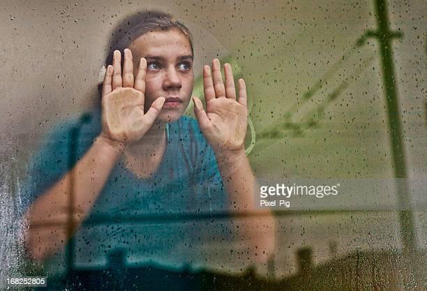 Niña mirando por la ventana (con reflejos de la ciudad