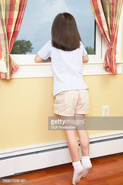 girl (5-7) looking out window, rear view - girls in socks stock photos and pictures
