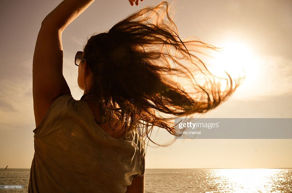 Girl looking the sea w/ hair in the wind at sunset : Foto stock