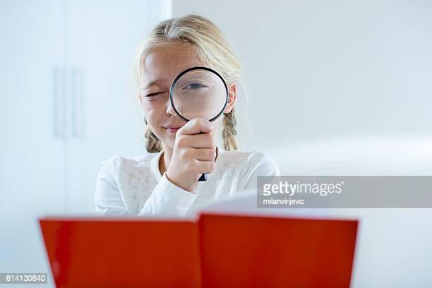 Menina Olhando através de uma lupa