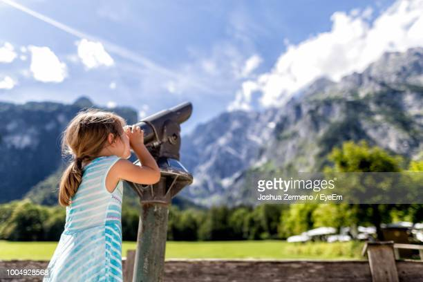 girl looking through binoculars against mountains - berchtesgaden stockfoto's en -beelden