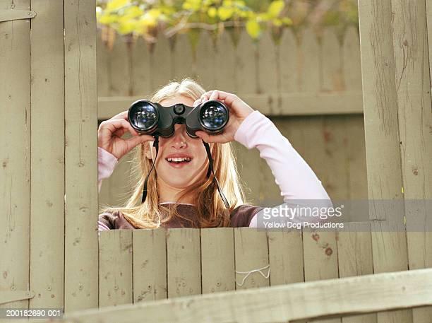 Girl (10-12) looking through binoculars from treehouse window