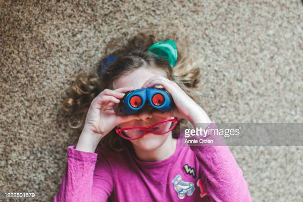 girl looking through binoculars the wrong way - binoculars stock pictures, royalty-free photos & images